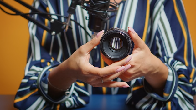 Close-up van de maker van inhoud die een recensie maakt voor nieuwe cameralens in professionele studioset. nieuwe media-sterbeïnvloeder op sociale media pratende video-fotoapparatuur voor online internetwebshow