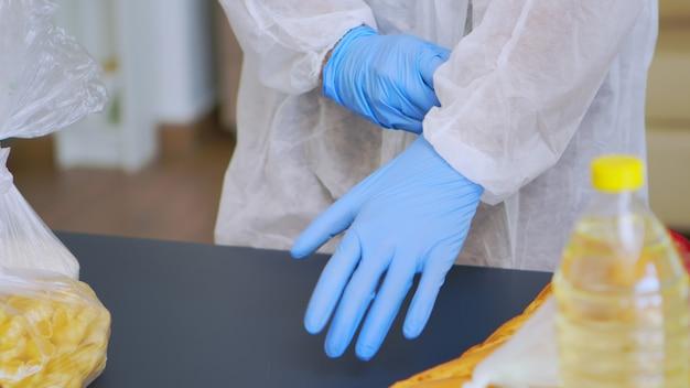 Close-up van de man die handschoenen aanbrengt voordat hij voedsel inpakt tijdens het coronavirus.