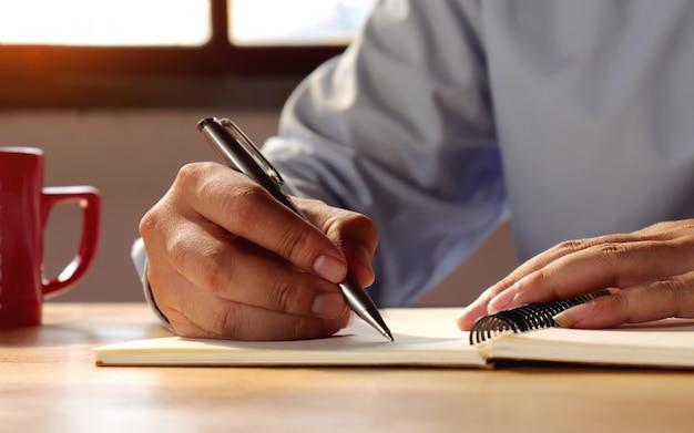 Close-up van de man die het spiraalvormige notitieboekje op de lijst met een rode koffiemok schreef