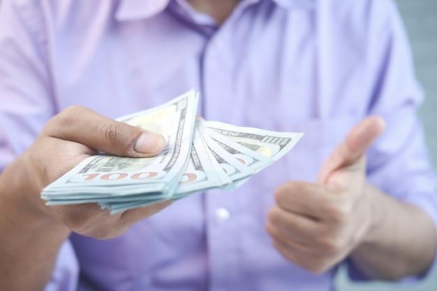 Close-up van de man die ons dollar vasthoudt en duimen laat zien