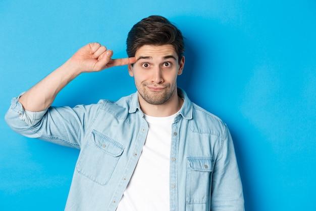 Close-up van de man die uitscheldt omdat hij dom of gek doet, vinger op het hoofd rolt en naar de camera kijkt, staande over een blauwe achtergrond