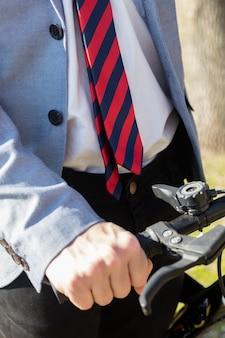 Close-up van de man draagt een pak en zijn fiets