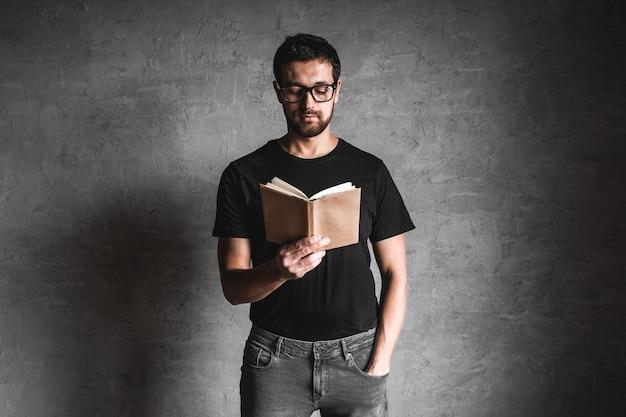 Close-up van de man in het zwarte boek van de t-shirtholding op geïsoleerd grijs