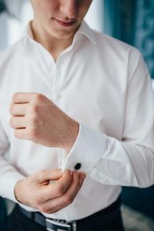 Close-up van de man in shirt verkleden en stropdas op nek thuis aan te passen.