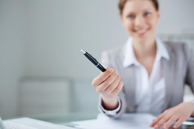 Close-up van de manager met een pen met onscherpe achtergrond