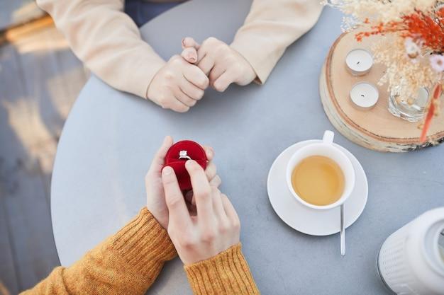 Close-up van de mens die de doos met ring opent en een voorstel doet aan zijn vriendin tijdens hun date in het restaurant