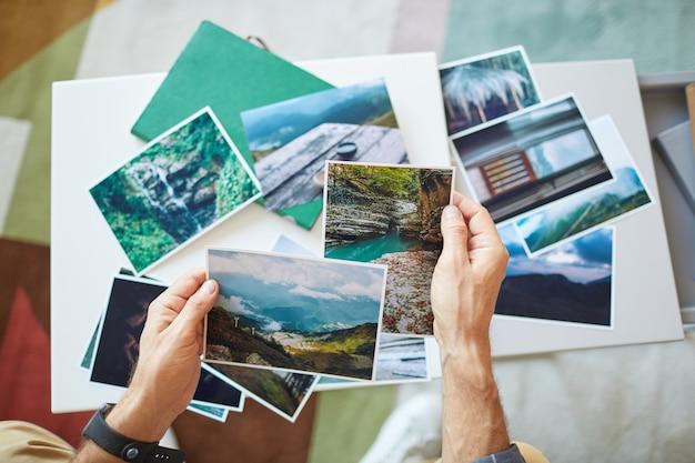 Close-up van de mens die de foto's voor collage kiest of een kaart van verlangens aan tafel maakt