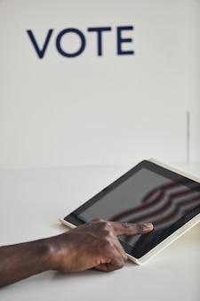 Close-up van de mens die digitale tablet gebruikt om tegen de witte achtergrond te stemmen