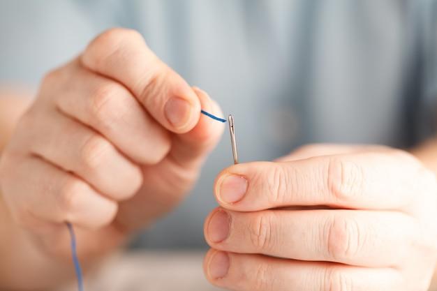 Close-up van de mens die draad trekt in de naald