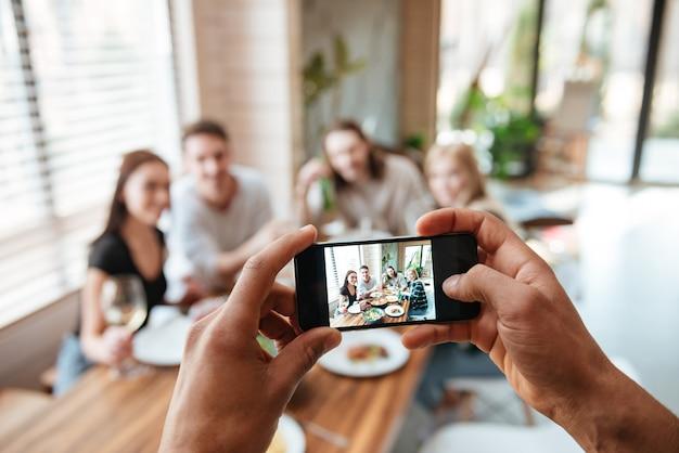 Close-up van de mens die foto's van vrienden met mobiele telefoon