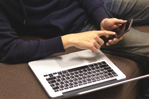 Close-up van de mens die gebruikend smartphone en laptop computerzitting op bank ontspannen.