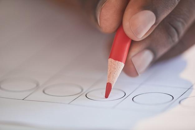 Close-up van de mens die het vinkje op de stemming zet met rood potlood tijdens de stemming