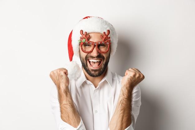 Close-up van de mens die kerstmis of nieuwjaar viert, een kerstfeestbril en kerstmuts draagt, zich verheugt en schreeuwt van vreugde, staand