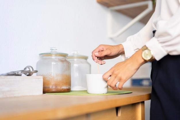 Close-up van de mens die koffie maakt op kantoor