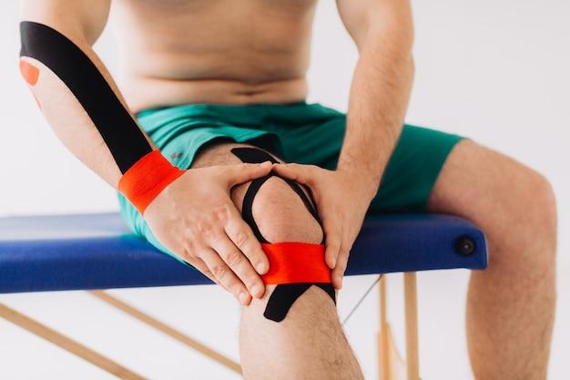 Close-up van de mens die lijden aan pijnlijke gewonde knie na sportblessure.