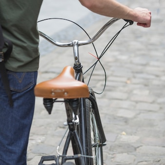 Close-up van de mens die met zijn fiets loopt