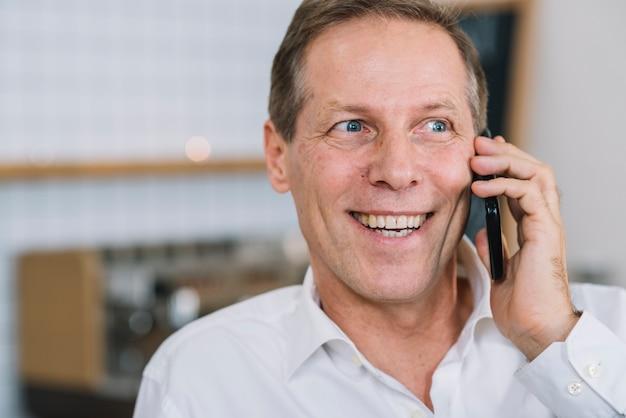 Close-up van de mens die op telefoon spreekt