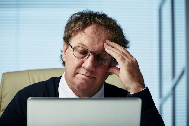 Close-up van de mens die over bedrijfsuitdagingenogen overweegt die in zijn bureau worden gesloten