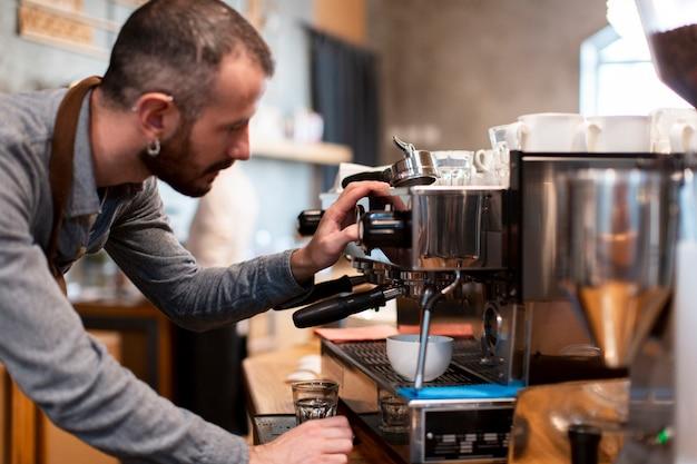 Close-up van de mens die schort draagt die in koffiewinkel werkt