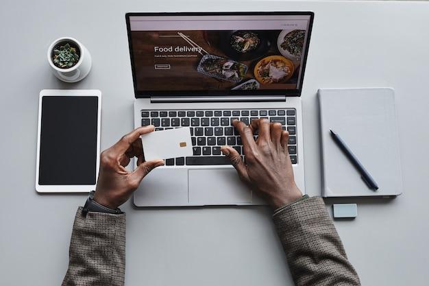 Close-up van de mens die voor online orde met creditcard betaalt die hij voedsel op laptop opdracht geeft