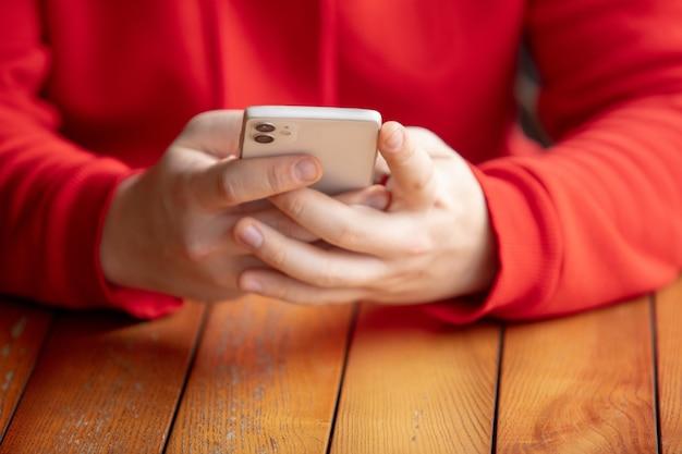 Close-up van de mens met behulp van mobiele slimme telefoon geïsoleerd op een witte muur. levensstijl, modern technologieënconcept.