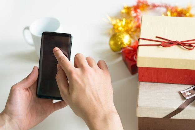 Close-up van de mens met behulp van smartphone aan tafel met kerstcadeaus
