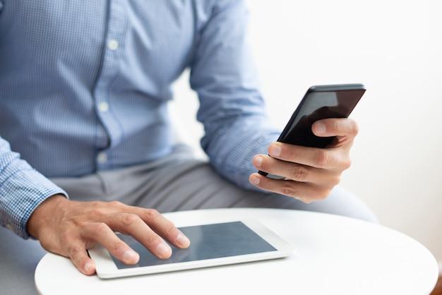 Close-up van de mens met behulp van smartphone en tablet aan de koffietafel