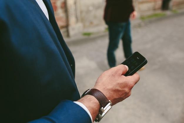 Close-up van de mens met horloge met zijn mobiele telefoon