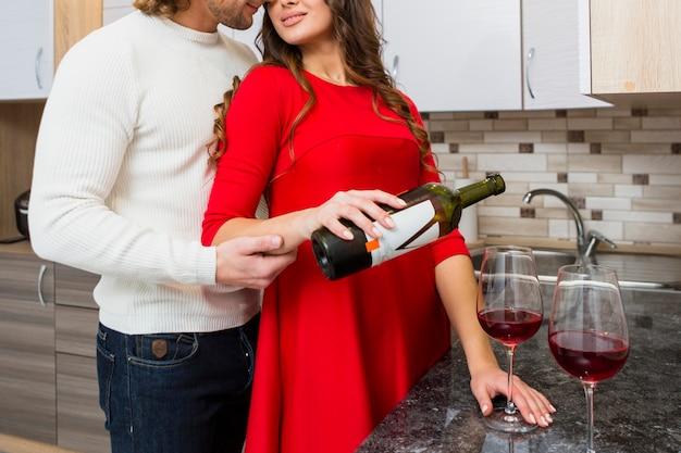 Close-up van de mens omarmen zijn vriendin gieten wijn in glas