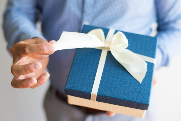 Close-up van de mens ontkoppeling boog tijdens het openen van cadeau