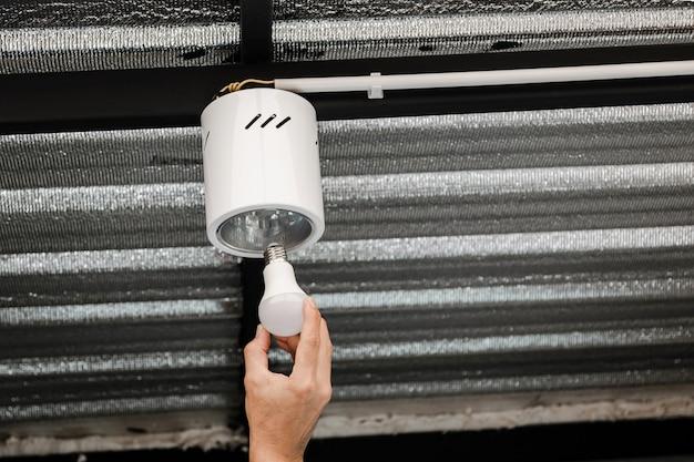 Close-up van de menselijke hand is het installeren van een led-lamp in een ronde plafondlamp.
