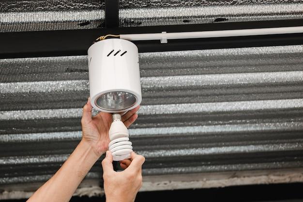 Close-up van de menselijke hand is het verwijderen van een fluorescerende lamp in een ronde plafondlamp om er een led-lamp van te maken.