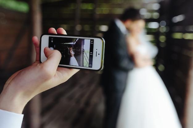 Close-up van de mobiele het nemen van een foto van de pasgetrouwden