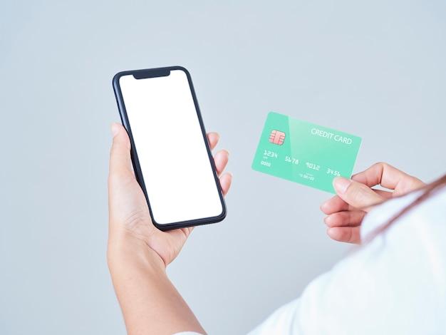 Close-up van de mobiele telefoon van de vrouwengreep, leeg scherm en creditcard op grijze achtergrond