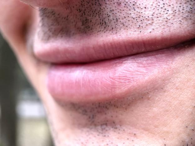 Close-up van de mond van een lachende man met een kleine stoppelbaard. delen van het menselijk lichaam, lippen.