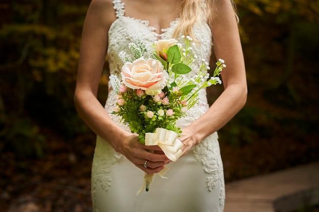Close-up van de mooie jonge bruid met een boeket in het bos