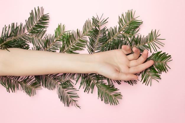 Close-up van de mooie vrouw hand kerstboom tak op de roze achtergrond, met kopie ruimte opleggen. reclame concept van schoonheid alleen vóór kerstmis. huidbehandeling.