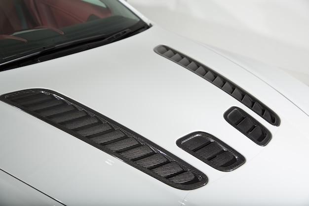 Close-up van de motorkap van een witte sportwagen onder de lichten