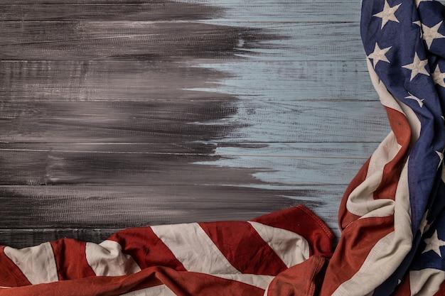Close up van de nationale usa amerikaanse vlag zwaaien op houten achtergrond met kopie ruimte voor tekst.