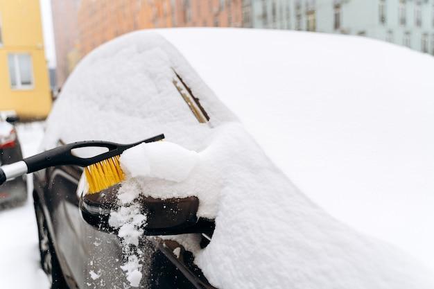 Close-up van de onherkenbare persoon die de auto uit de sneeuw schoonmaakt met de speciale borstel. apparaat voor het reinigen van sneeuw uit het autoconcept. stock foto
