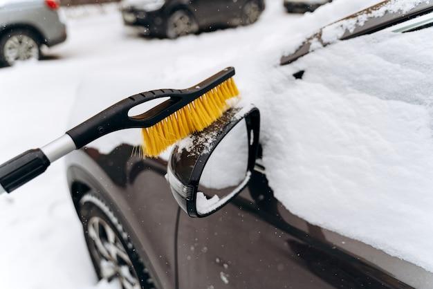 Close-up van de onherkenbare persoon die de auto uit de sneeuw schoonmaakt met de speciale borstel. winter en cyclonen concept