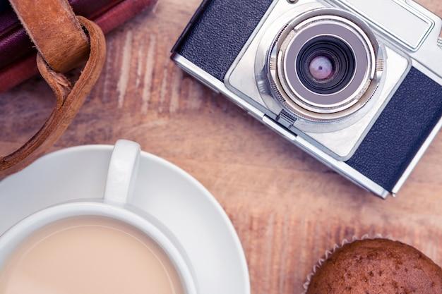 Close-up van de oude camera met dagboeken en koffie op tafel