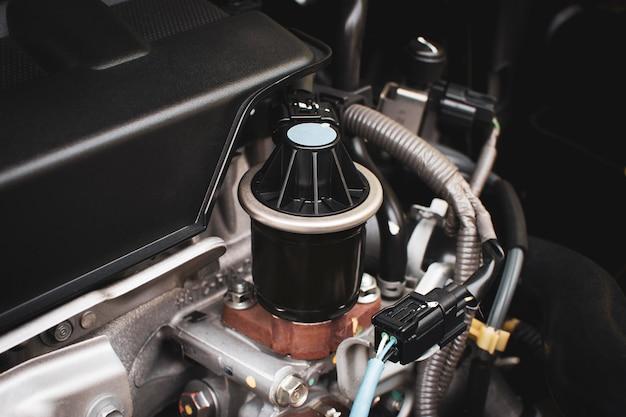 Close up van de oude uitlaatgasrecirculatie in het motorcompartiment om het koolmonoxidegas uit de uitlaat te verminderen. auto-onderdeel concept.