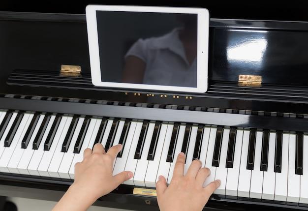 Close-up van de pianist met tablet inoefenen