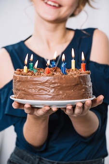 Close-up van de plaat van de de handholding van het meisje van chocoladecake met aangestoken kaarsen