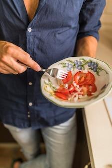 Close-up van de plak van de mensenholding van tomaat met vork