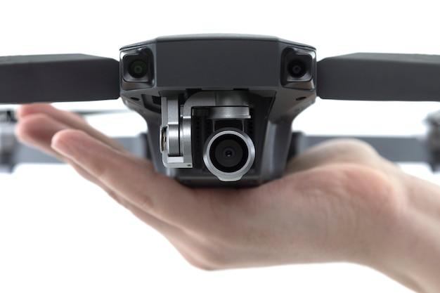 Close - up van de quadcopter camera op de palm van een man op een wit