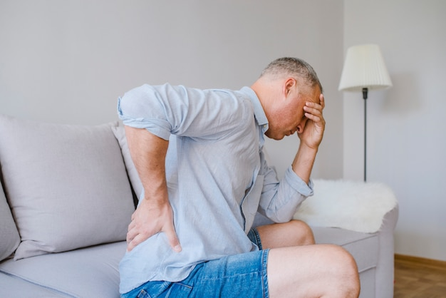 Close-up van de rijpe mens die aan pijnrug lijden terwijl thuis het zitten op bed,