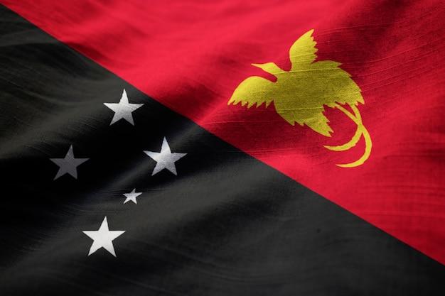 Close-up van de ruffled vlag van papoea-nieuw-guinea, de vlag die van papoea-nieuw-guinea in wind blazen