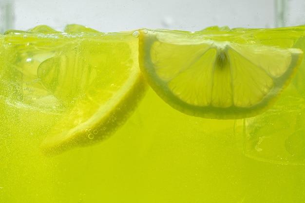 Close-up van de schijfjes citroen in limonade muur.